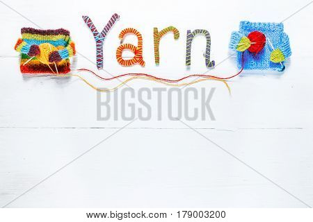 Knit shop background with text 'Yarn' of handmade colorful letters and funny cozy sweater characters. White painted wood background