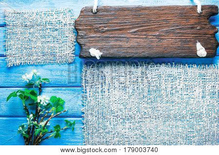 Background of narrow wood planks painted in blue. Bunch of blooming apple tree and young black current twigs. Wood signboard as title bar