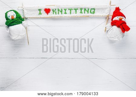 Knit shop background with hand-knitted title 'i love knitting' and couple of handmade snowmen of yarn skeins holding wool balls. White wood background