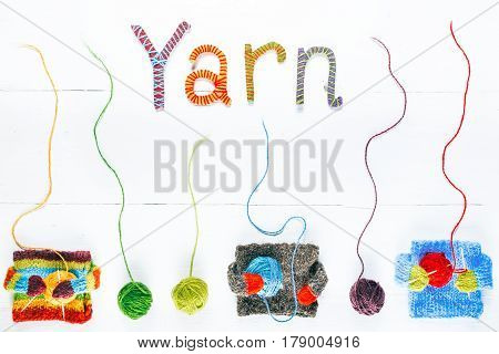Knit shop background with text 'Yarn' of handmade letters. Tiny cozy sweaters holding colorful wool balls. White painted wood background