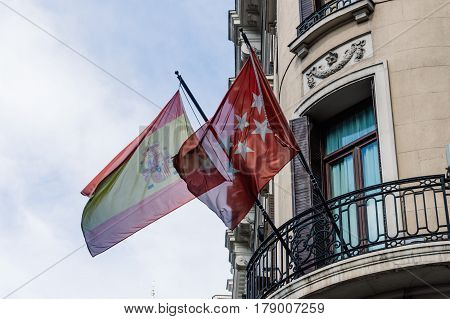 Madrid Spain - September 18 2016: Low angle view of balcony with spanish and Madrid flags at Gran Via Street in Madrid.
