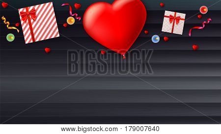 Red inflatable balloon in the shape of a heart with gift boxes, candles, tinsel and confetti on wooden background. Template for creative persons. Best background for holiday, festive greetings cards.