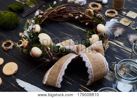Top view of a preparatory elements for Easter holiday. Easter workshop of wreath, decor, candles, twigs and green moss