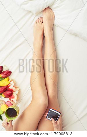 Overhead shot of slim long female hands isolated on the bed. Cropped shot of female lying on the bed. Drinking tea. White bed. Flowers lying on the white surface