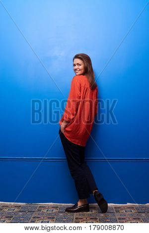 Full-length shot of a smiling brunette half-turned posing in the studio. Isolated over blue background