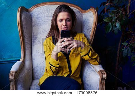 Close-up of an intent girl looking attentively at the screen of a smartphone. Sitting in a comfortable armchair. Obscure atmosphere in the room