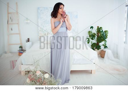 Cute girl with makeup in a blue evening dress standing beside the bed.