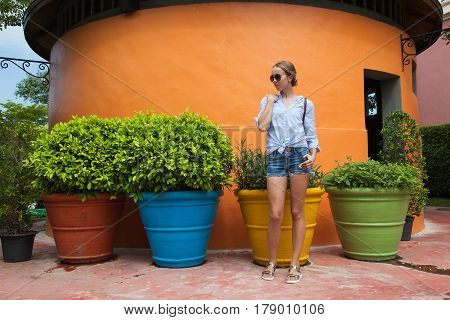 Portrait of a young slender woman standing in front of a bright orange wall in a park.