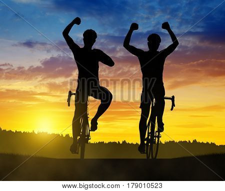 Two cyclist riding a road bike at sunset.