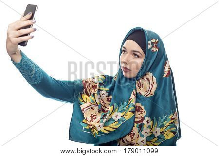Middle Eastern or East European female proudly showing her conservative fashion via social networking by taking a selfie with a cell phone camera. The headscarf is associated with muslim culture.
