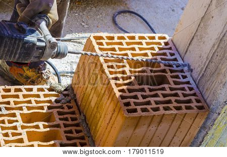 Mason drills a hole with a power drill on a column in of reinforced concrete. Selective focus on drill