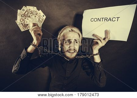 Stress at work no freedom pursuit of money concept. Scared man with chained hands holding money and contract studio shot on dark grunge background