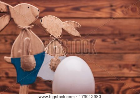 couple of wooden easter bunnies near a big egg with copyspace on old wood background