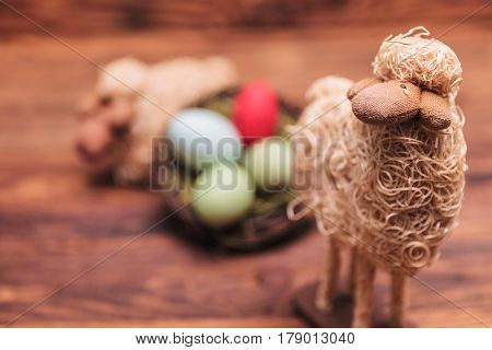 easter toy sheep in fron of egg basket on old wood background