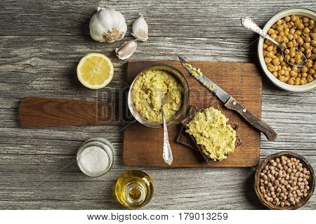 Classic hummus chickpeas with bread on wooden background