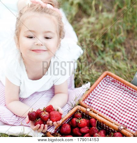 Smiling kid girl 4-5 year old eating strawberry in park. Healthy lifestyle. Summer time.