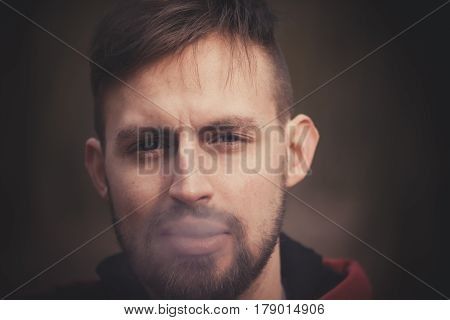 handsome stylish young man smoking outside in urban setting