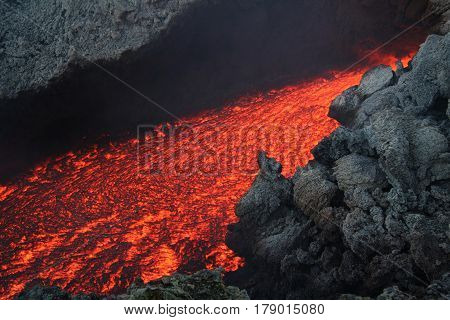 Closeup of red volcanic lava flow in rocky landscape.