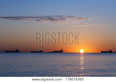 Side view of silhouetted tanker ship with orange sunset background.