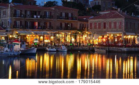 MOLYVOS, LESVOS, GREECE - JUNE 12, 2014: Holiday makers dining in harbor side restaurants Molyvos Greece