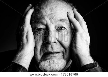 Black-and-white portrait of a smiling old man over black background. Old age concept.
