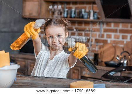 Adorable Girl With Spray Bottles And Different Cleaning Supplies At Home