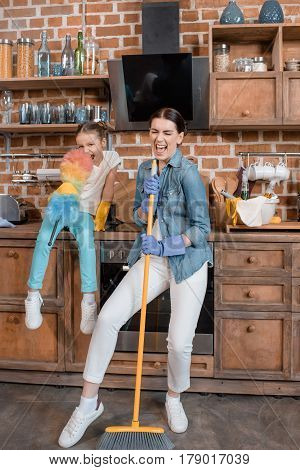 Happy Mother And Daughter With Duster And Broom Having Fun While Cleaning Home