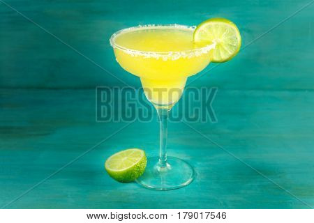 Lemon Margarita cocktail with wedges of lime on a turquoise background with copy space