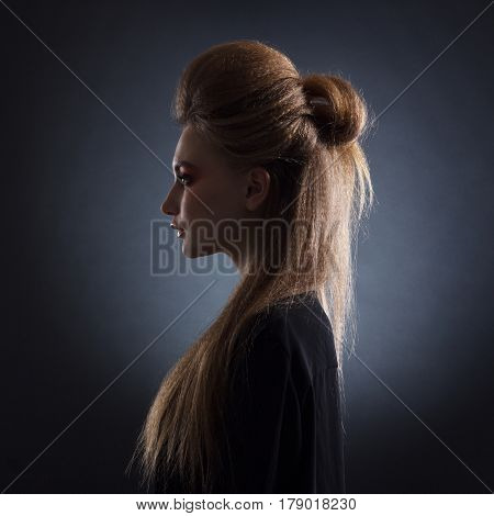 Portrait of woman with stylish hairstyle in profile against a dark background.