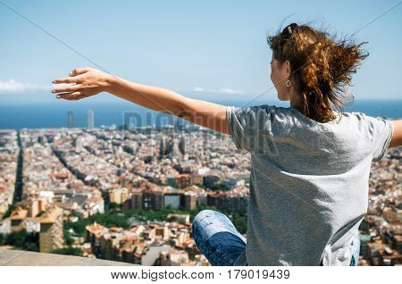 Young happy woman sits back to the camera with raised hands. Traveler enjoying the cityscape of mountain Barcelona Catalonia Spain
