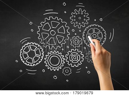 Female hand holding white chalk in front of a blackboard with gears drawn on it