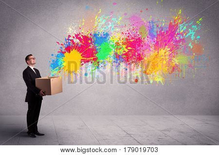 A young smiling business male holding a paperboard box with illustration of colourful spray paint splash on urban wall background concept.