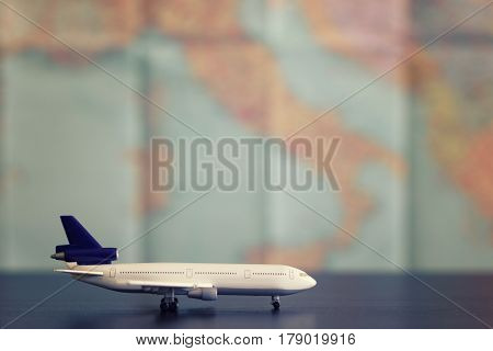 Model aircraft on a background map of the world. The concept of travel.