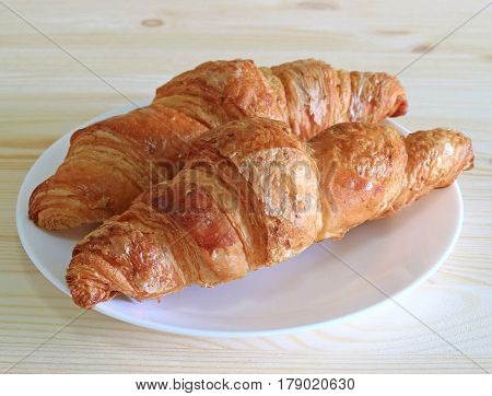 Pair of fresh whole wheat Croissant pastries served on a white plate