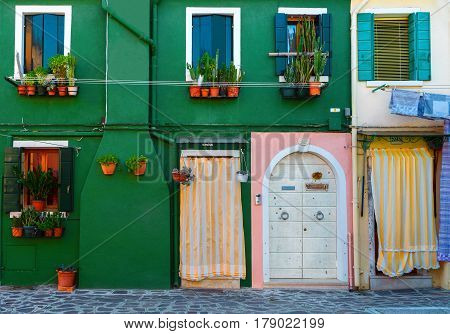 BURANO, ITALY - 2 Septenber,  2016.Beautiful facade in Veneto, Burano Island. Decorative textured green grunge and colorful house wall with a door and a window