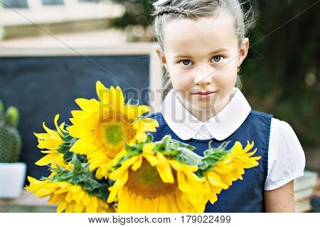 Portrait of a beautiful young first-grader with bouquet of sunflowers in a festive school uniform on the background spring park. Farewell Bell. day of knowledge. beginning of the school year.