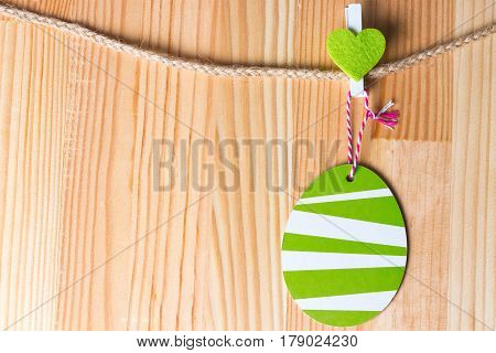 Greenery heart and easter egg on a twine. Natural wooden background. Copy space on the left.