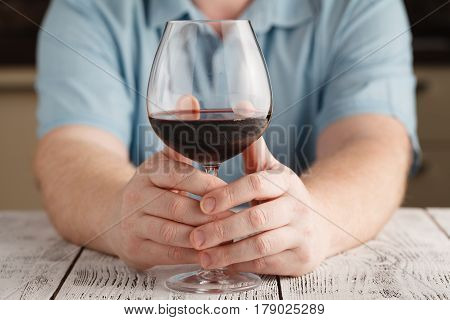 Man Sitting At Table Having A Glass Of Red Wine