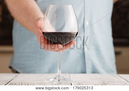 Leisure, Drinks And Lifestyle Concept - Close Up Of Male Hand Holdind Glass Of Red Wine