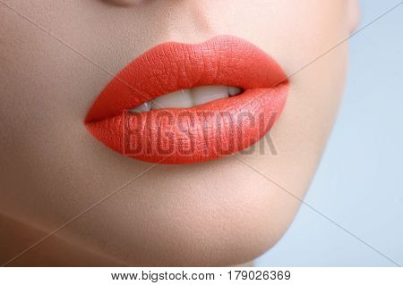 Beautiful full lips. Cropped beauty close up of sexy full female lips covered with orange lipstick face mouth open white teeth augmentation fillers cosmetology procedure treatment sexy plump concept