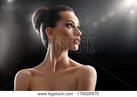 Fresh beauty. Stunning beautiful young woman with perfect skin and healthy hair in a bun posing sensually looking away on black background lens flare copyspace beauty perfection cosmetic treatment