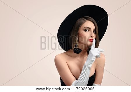 Gorgeous young red lipped woman shushing to the camera wearing elegant black dress hat and long gloves copyspace fashion style beauty brunette cosmetics lifestyle secret shush quiet .
