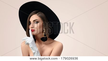 Horizontal studio portrait of a beautiful fashion model wearing a hat and gloves making shushing gesture to the camera copyspace beauty cosmetology skincare secrecy silence concept .