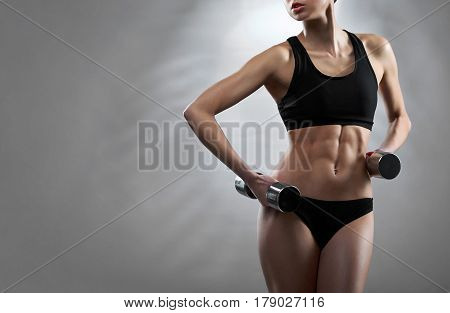 Good example. Cropped studio shot of a healthy young fitness woman showing off her perfect abs holding dumbbells against grey background