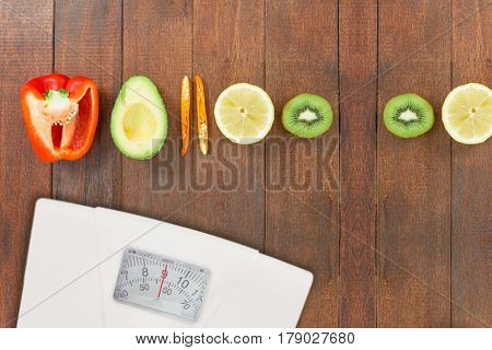 weighting scale against overhead view of various half cut vegetables and citrus fruits