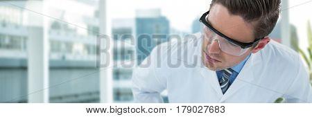 Doctor wearing protective eyewear against laptop on desk by glass window in office