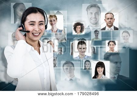 Smiling businesswoman using headset against dark blue background