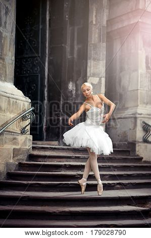 Statuesque ballerina. Young ballerina wearing all white practicing in an old castle