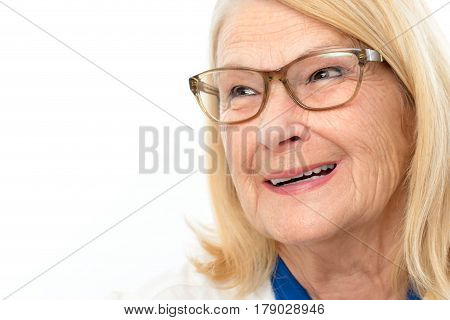 Close up macro portrait of happy smiling senior woman.Blond lady wearing glasses looking aside isolated on white background.