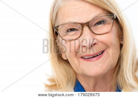Close up face shot of attractive senior woman with charming smile.Blond lady wearing glasses isolated on white background.